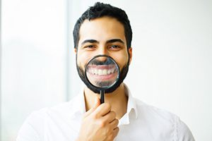 man holding magnifying glass to smile to show off dental crowns in South Portland