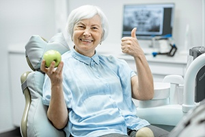 Female patient smiling and giving thumbs up in dental chair