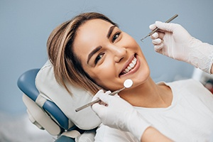 Woman smiling with dental implants in dentist's chair