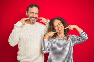 Happy, mature couple after receiving implant-retained prosthetic teeth